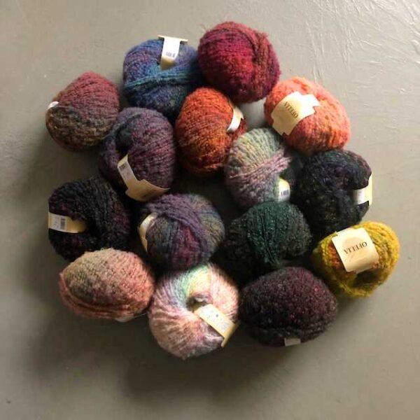 Garnnøgler med uldgarn i blå, rød, gul, grøn, lilla