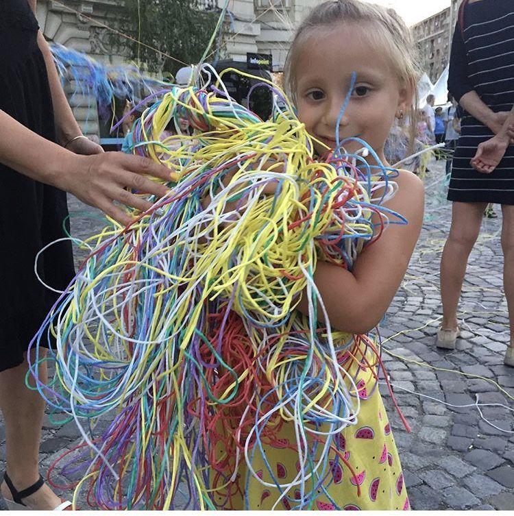 En glad pige med favnen fuld af garn